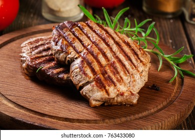Succulent portions of grilled fillet mignon served with rosemary on an wooden board