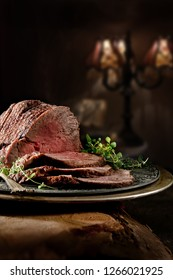 Succulent prime roast beef topside rump joint carved and ready for serving. Shot against a rustic background with generous accommodation for copy space.