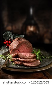 Succulent prime roast beef topside rump joint carved and ready for serving. Shot against a rustic, festive background with generous accommodation for copy space.