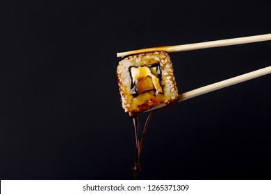 succulent roll between chopsticks on black background, drops of soy sauce appetizingly dripping from sushi, food background, Japanese cuisine concept
