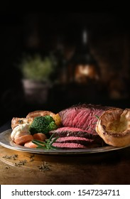 Succulent side of rare roast beef with seasonal vegetables, Yorkshire Puddings and roast potatoes with Rosemary garnish shot in a rustic setting with an old fashioned wood burner. Copy space.