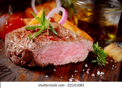 Succulent tender rare beef steak grilled to perfection sliced through to show the texture seasoned with fresh rosemary and salt