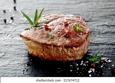 Succulent thick grilled beef steak trimmed for fat for a healthy diet on a griddle with a sprig of fresh rosemary and seasoned with salt and peppercorns
