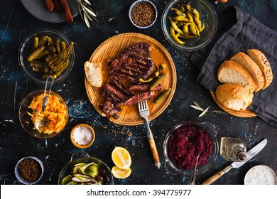 Succulent thick juicy portions of grilled fillet steak served with variety veggies dips, fermented veggies, cucumber and pepper marinated, bread buns on a old vintage table  Authentic dinner party.