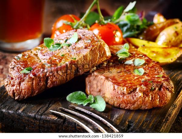 Sukkulente, saftige Portionen von gegrilltem Filet Steak, serviert mit Tomaten und Bratgemüse auf einem alten Holzbrett
