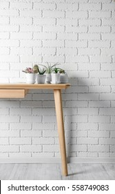 Succulents and cactus on wooden table on white brick wall background