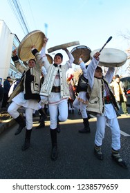 Suceava, Romania - December 27, 2017: Young men and boys dress in national costumes and with big drums perform traditional Romanian dance during annual festival of winter pagan rituals od Malanca.