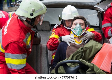 Suceava/Romania - 05 14 2014: National Emergency drill - Firefighters helping wounded young man in car accident
