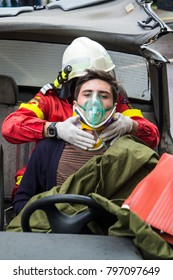 Suceava/Romania - 05 14 2014: National Emergency drill - Firefighter helping wounded young man in car accident
