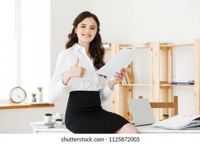 Sucessful business Concept: Attractive young female showing thumbs up and holding document in an office
