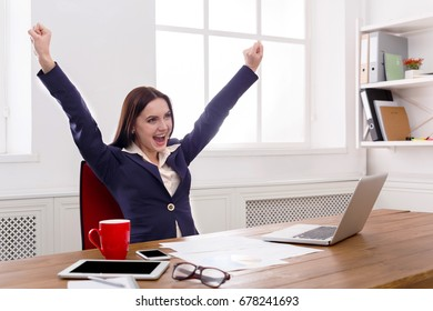 Sucessful project. Happy business woman sitting at table in office and keeping arms outstretched , enjoying new achievement.
