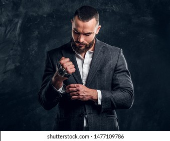 Sucessful serious man is posing for photographer with watch on his fist on the dark background.