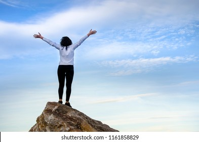 Sucessfull girl open hand on top of mountain summit rock