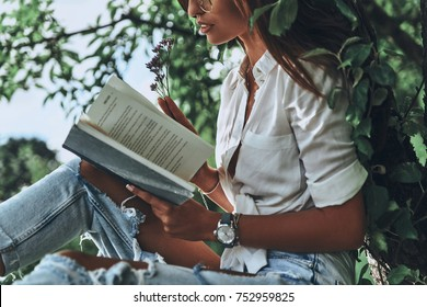 Such an interesting book! Close-up of young woman holding an open book while sitting on the tree outdoors