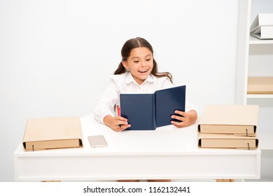 Such interesting topic. Girl child read book while sit table white interior. Reading textbook. Schoolgirl studying textbook. Kid girl school uniform happy face read book. Excited about right answer.