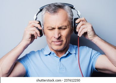 Such music is not for me. Portrait of frustrated senior man in headphones listening to music keeping eyes closed while standing against grey background