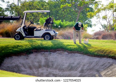 Sucina, Spain - August 08 2018: A groundsman on a golf course, taking soil samples from the fairway near a bunker with an augur.