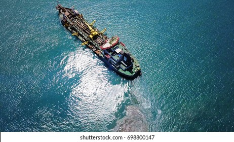 Suction Dredger ship working near the port - with mud, Pollution, brown Muddy water - aerial shot