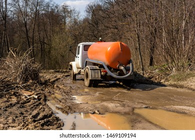 Suction truck driving on a terrible dirty road