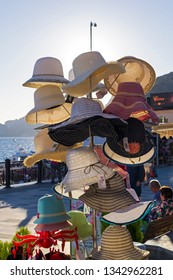 Sudak, Crimea - September 28, 2018: A hanger with female summer hats in a store on the waterfront of the resort town of Sudak. Crimea, a sunny day in early September.