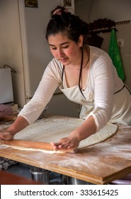 Sudak, RUSSIA - May 15 2015: Young beautiful girl rolled the dough and prepare the national Crimean Tatar meal pasties in a small kitchen, a fast food restaurant. Crimean - Tatar national cuisine