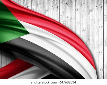 Sudan flag of silk with copyspace for your text or images and wood  background -3D illustration