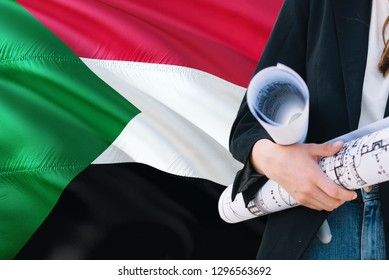 Sudanese Architect woman holding blueprint against Sudan waving flag background. Construction and architecture concept.