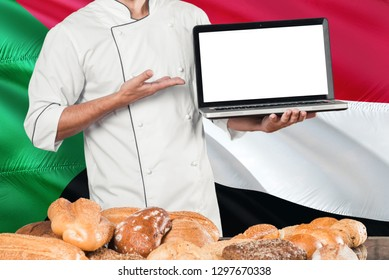 Sudanese Baker holding laptop on Sudan flag and breads background. Chef wearing uniform pointing blank screen for copy space.