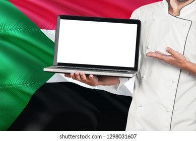 Sudanese Chef holding laptop with blank screen on Sudan flag background. Cook wearing uniform and pointing laptop for copy space.