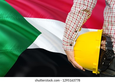 Sudanese Engineer is holding yellow safety helmet with waving Sudan flag background. Construction and building concept.