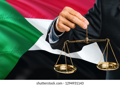 Sudanese Judge is holding golden scales of justice with Sudan waving flag background. Equality theme and legal concept.