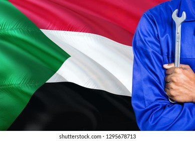 Sudanese Mechanic in blue uniform is holding wrench against waving Sudan flag background. Crossed arms technician.