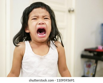 A sudden burst of crying of an upset Asian baby girl, 29 months old, at home, baby behavior