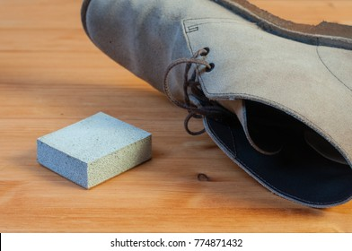 A suede eraser and a paire of suede boots on a wooden table