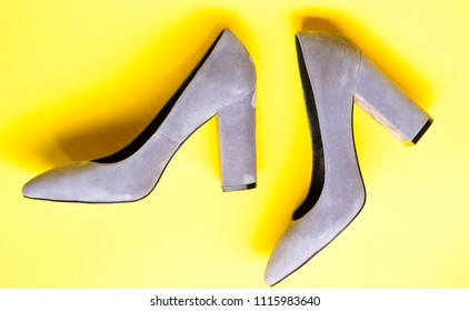 Suede footwear concept. Shoes made out of grey suede on yellow background. Footwear for women with thick high heels, top view. Pair of fashionable high heeled shoes.