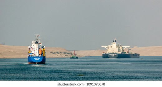 Suez Canal, Egypt - December 13 2012 A VLCC tanker and a small container ship northbound in the Suez Canal. By regulation, the VLCC is trailed by a tugboat, in case of an engine or steering failure.