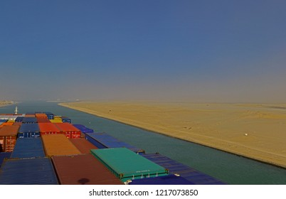 suez canal, egypt - january 06, 2105 -- the containership cma cgm vela ( imo 9354923)  transiting the suez canal near km 82 during a sandstorm, background:   ismailia city  and  lake timsah