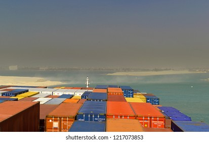 suez canal, egypt - january 06, 2105 -- the containership cma cgm vela ( imo 9354923)  transiting the suez canal near km 80e during a sandstorm, background:   ismailia city  and  lake timsah