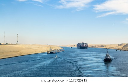 Suez Canal, Egypt - November 5, 2017: Long pantone bridge, transported by tugboats, along western bank of Suez Canal, on background: ship's  convoy with Maersk line cargo vessel container, Egypt