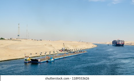 Suez Canal, Egypt - November 5, 2017: Pantone bridge, transported by tugboats, along western bank of Suez Canal, on background: ship's convoy with Maersk line cargo vessel container ship, Egypt