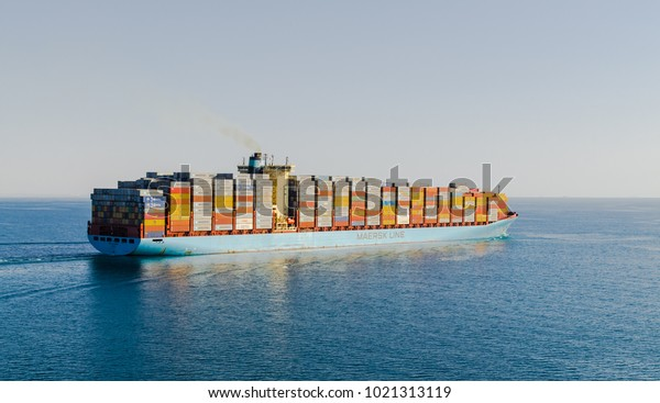 Suez Canal, Egypt-November 5, 2017: Maersk line cargo vessel container ship passing Suez Canal, sun set. GEORG MAERSK is registered and sailing under flag of Denmark, her gross tonnage -98648