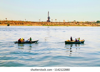 Suez Canal near Ismailia / Egypt -  September 12 2015: Two little fisher boats on the New Suez Canal with on the other side the monument of the canal, Egypt