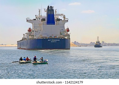 Suez Canal near Ismailia, Egypt / September 12 2015:  Cargo ship crossing the new canal of Suez near Ismailia and two little fisher boats, Egypt