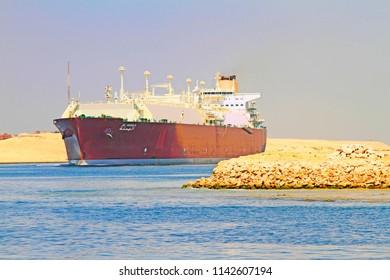 Suez Canal near Ismailia, Egypt / September 12 2015:  Cargo ship crossing the new canal of Suez near Ismailia, Egypt
