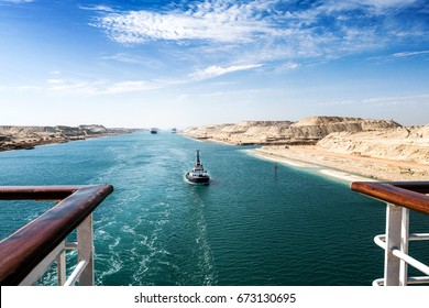 The Suez Canal - a ship convoy with a cruise ship passes through the new eastern extension canal, opened in August 2015, landscape format with a ship´s rail in the foreground left and right side