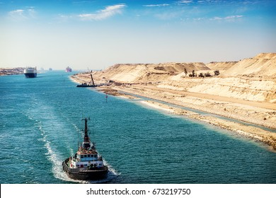 The Suez Canal - a ship convoy passes through the new eastern extension canal, opened August 2015,  a tugboat in the foreground