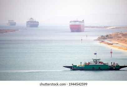 Suez Canal zone. Ship convoy in the distant desert haze. A local ferry between the east and west bank in foreground.