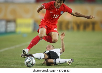 SUEZ, EGYPT - SEPTEMBER 29:  Young Cheol Cho of the Korea Republic (10) leaps over a tackle during a FIFA U-20 World Cup soccer match against Germany  September 29, 2009 in Suez, Egypt.