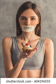 Suffering from anorexia. Girl is holding a cake and looking at camera, her mouth is sticked up with a word Food