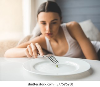 Suffering from anorexia. Girl is trying to put a pea on the fork